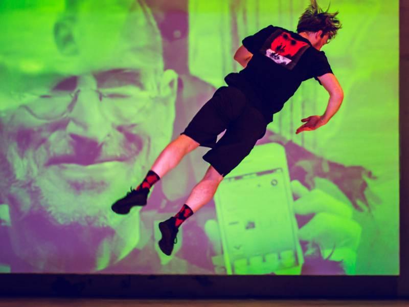 Mann springt vor einer Leinwand auf einer Bühne
