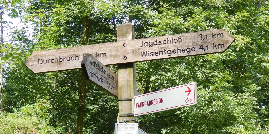 """Ein Wegweiser aus Holz in einem Wald, auf dem unter anderem """"Durchbruch"""", """"Jagdschloss"""" und """"Wisentgehege"""" mit Kilometerangabe ausgewiesen sind."""