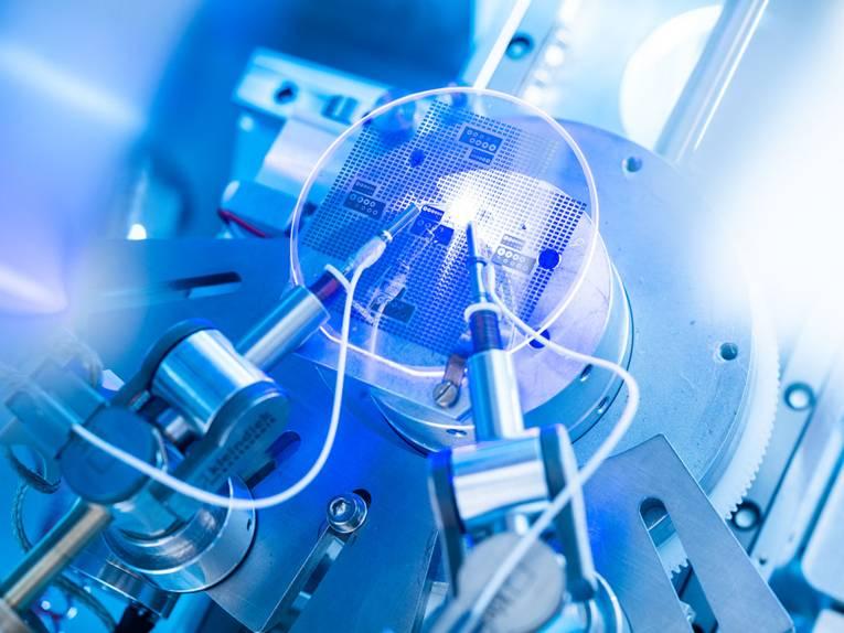 Ein Computerchip wird mit zwei spitzen Werkzeugen bearbeitet.