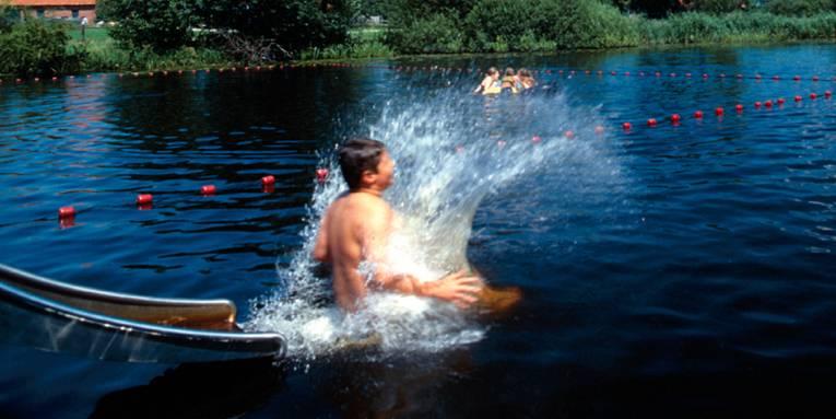 ein Junge ist gerade von der Rutsche gerutscht und taucht ins aufspritzende Wasser ein