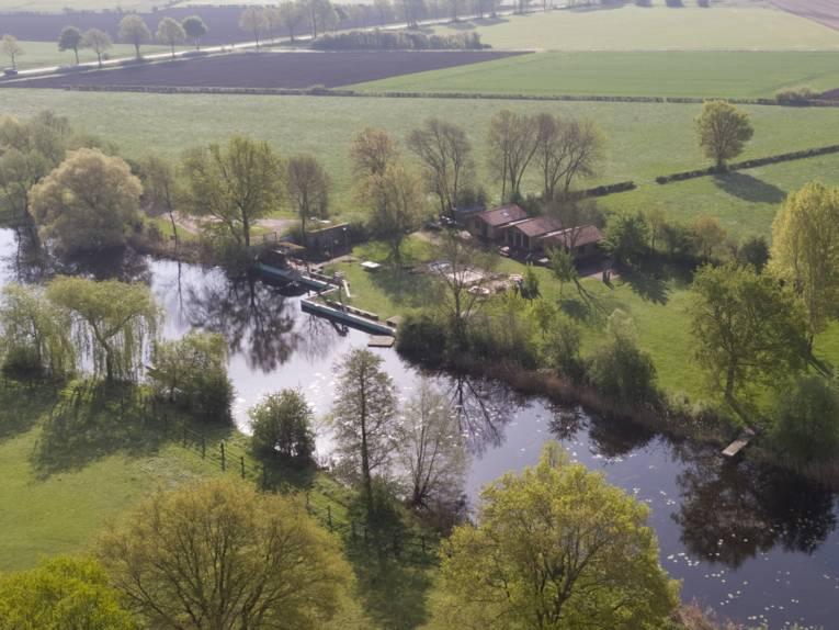 Luftaufnahme eines Natursees mit Gebäuden und Felder