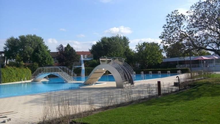 Das mit Wasser gefüllte Aussenbecken des Hallenfreibades Burgdorf ohne Badegäste bei schönem Wetter mit breiter Spaßrutsche, Sprungturm und Brücke