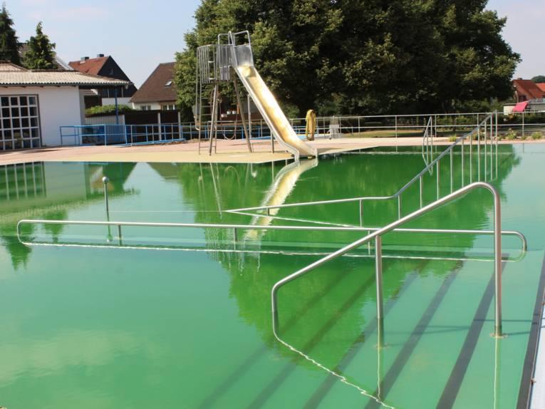 Ein Schwimmbecken, im Hintergrund eine Rutsche mit grünlich schimmerndem Wasser. Im Vordergrund Stufen, die ins Wasser führen.