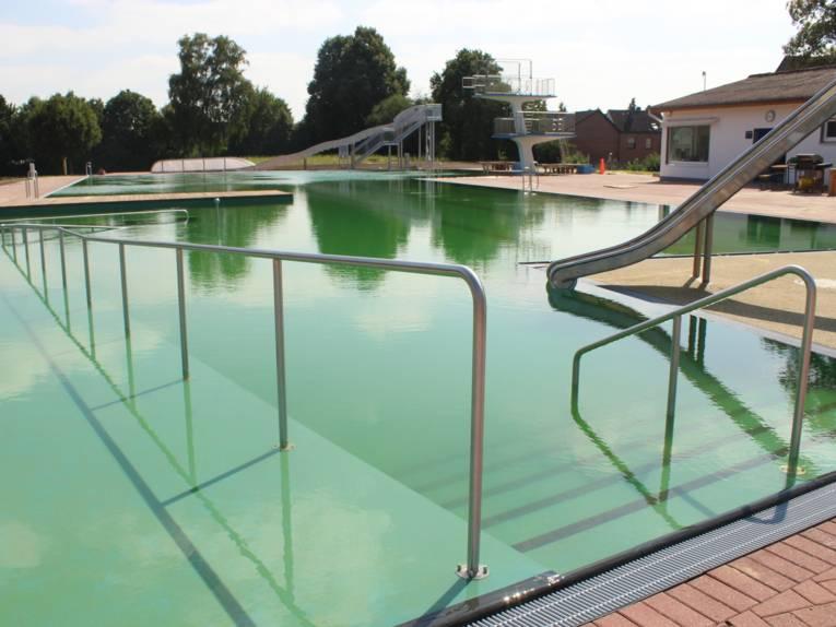 Einstieg ins Schwimmbecken über Stufen und mit Handläufen, rechts und im Hintergrund je eine Rutsche