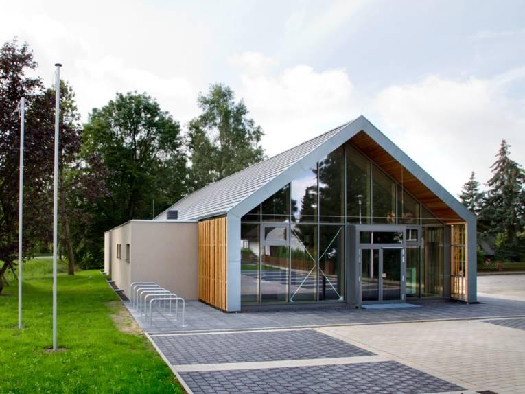 Energieeffizienter Hallenbau aus Glas, Stahl und Holz. Das Gebäude ist eingeschossig und hat ein spitzes Dach. An der linken Seite sind rechteckige Anbauten mit Flachdach.