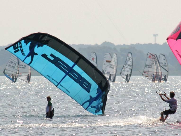 Eine Person steht auf einem Surfbrett und lässt sich von einem Lenkdrachen über das Wasser ziehen. Links ist ein blauer Lenkdrachen eines weiteren Kitesurfers zu erkennen, im Hintergrund sind Wassersportler als Windsurfer unterwegs.