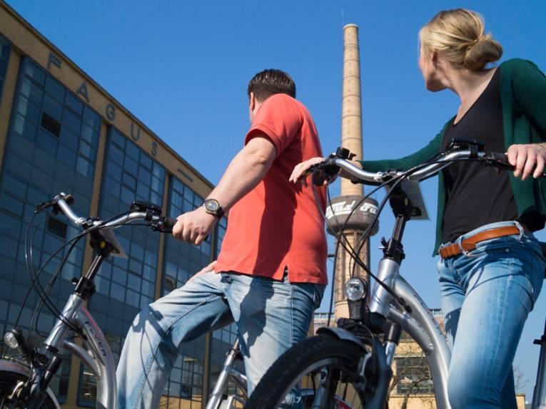 Zwei Radfahrer von einem Industriegebäude mit Schornstein