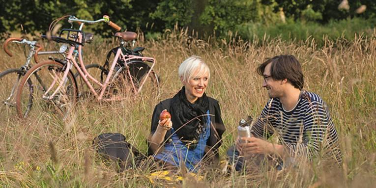 Zwei Personen, die auf einer Wiese sitzen, im Hintergrund zwei Fahrräder