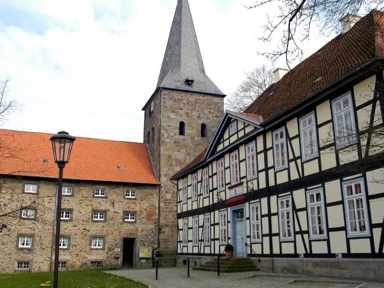 Blick auf die Klosterkirche mit romanischem Wehrturm, Rechts ist ein benachbartes Fachwerkgebäude zu sehen.