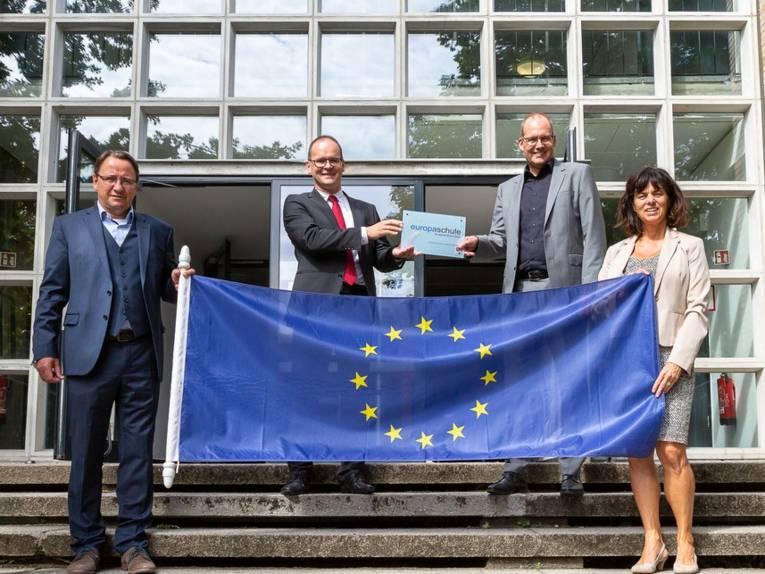Vier Personen auf einer Treppe vor einem Gebäude. Sie halten eine Europaflagge.