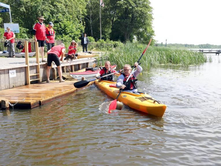Ein Boot mit zwei Personen legt von einer Kanueinsatzstelle ab.