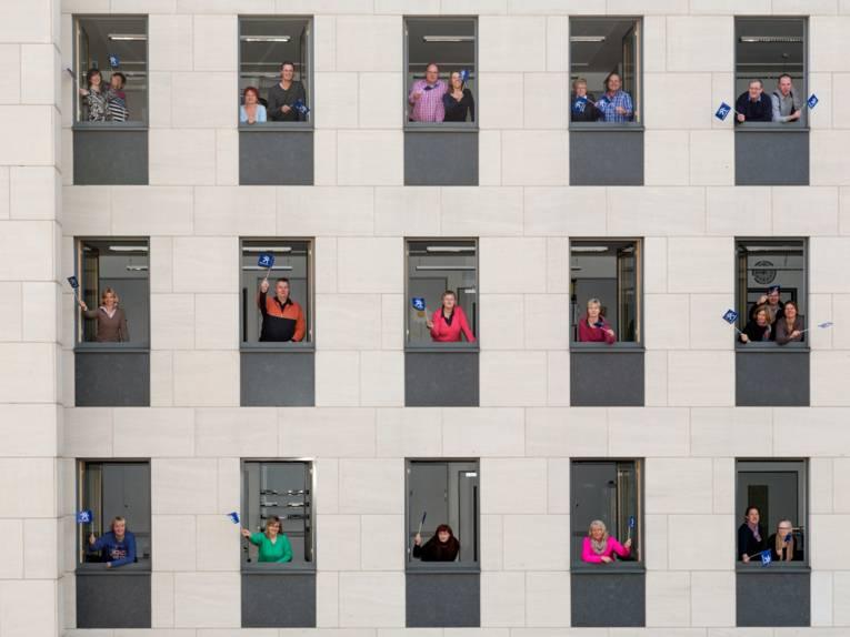 Beschäftigte schauen aus Bürofenstern und schwenken ein Regions-Fähnchen.