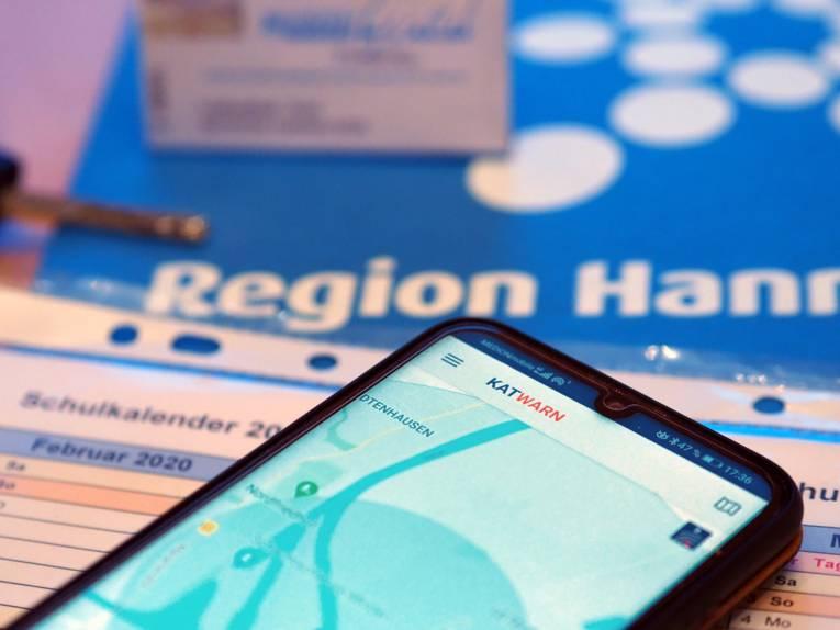 Auf einem Smartphone ist die Katwarn-App geöffnet. Das Smartphone liegt auf einem Schulkalender, drumherum sind ein Autoschlüssel, eine GVH Monatsfahrkarte und das Logo der Region Hannover.