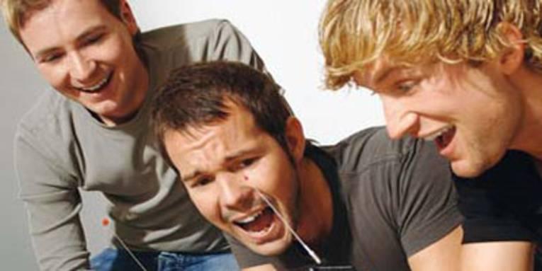 Drei Männer schauen begeistert auf Spielgeräte.