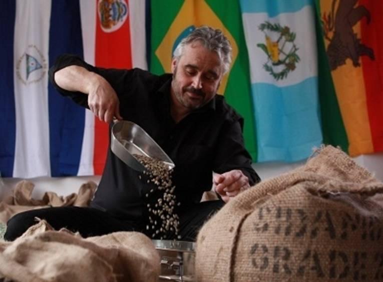 Ein Mann häuft Kaffee in einen Sack