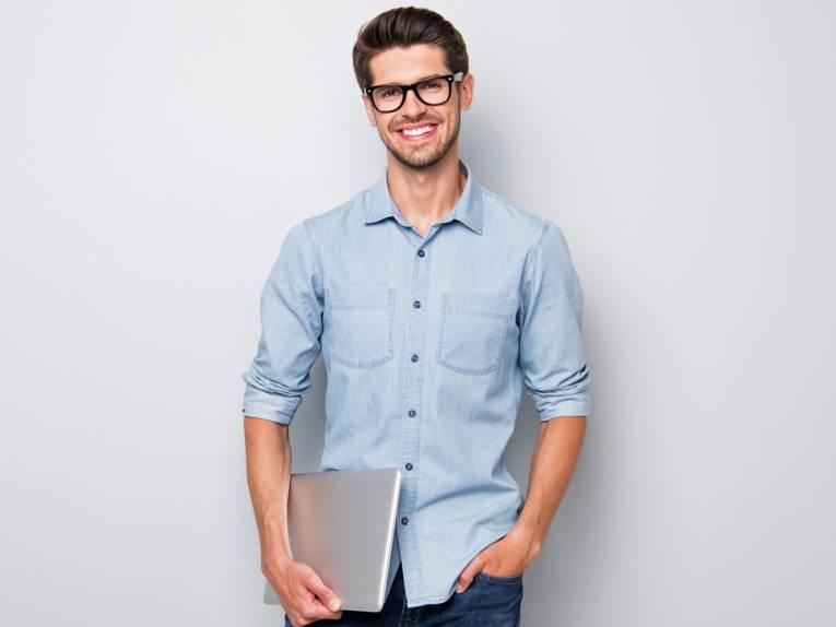 Ein Mann mit einem Laptop unter dem Arm