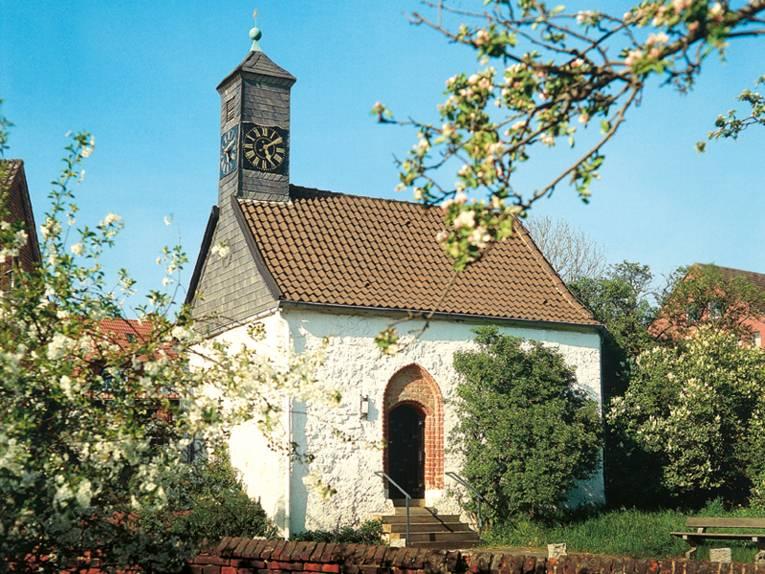 Kapelle mit weißem Mauerwerk und Schiffer gedecktem Turm