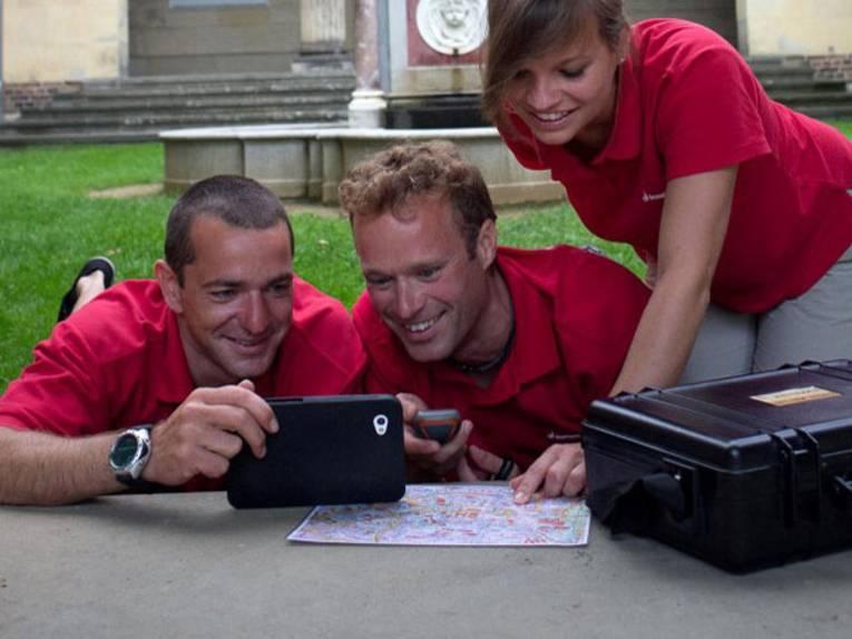 Personen über Landkarte und elektronische Geräte gebeugt
