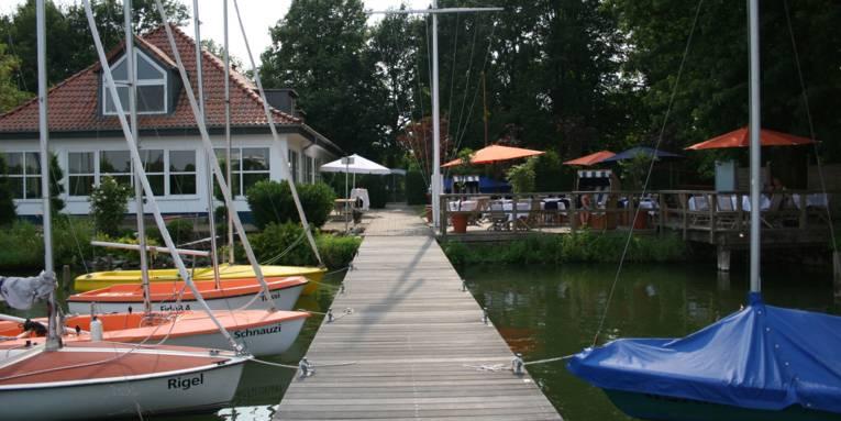 Haus an einem See mit Booten und Holzsteg