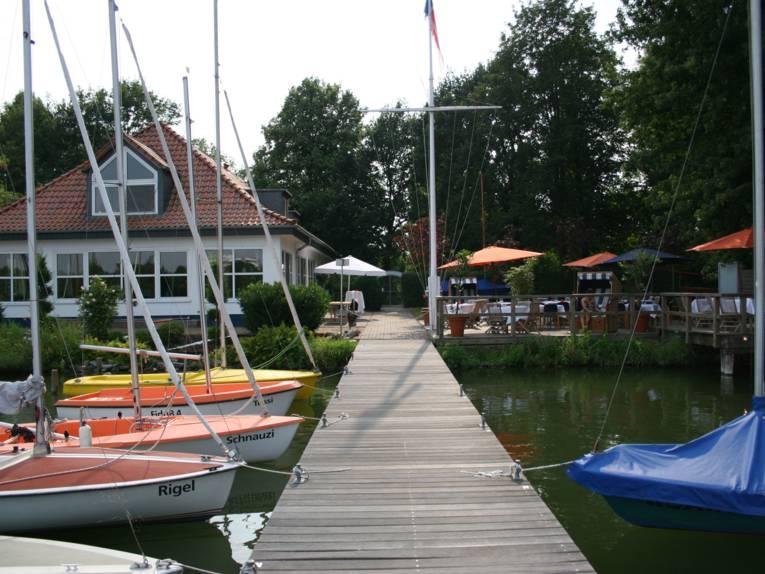 Haus am See mit Booten und Holzsteg