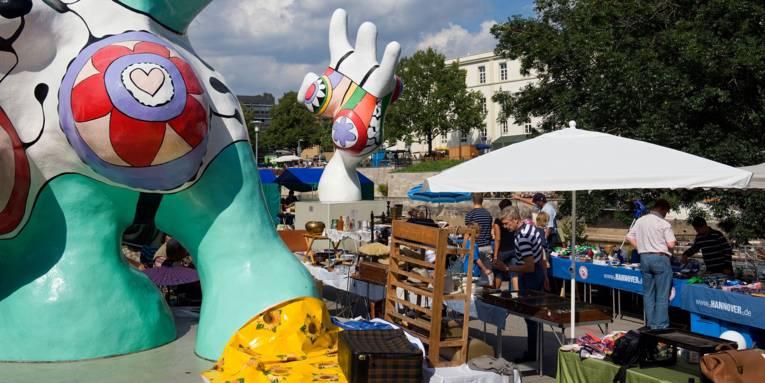 Man sieht mehrere Flohmarktstände und zwei Nana Figuren am Hohen Ufer in Hannover.