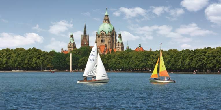 Maschsee mit Blick auf das Rathaus. Auf dem Maschsee befinden sich zwei Segelboote.