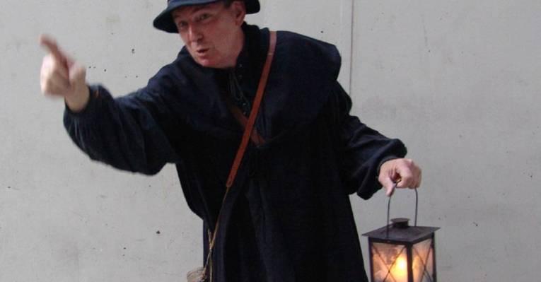 Ein Mann in einem Kostüm hält eine Lampe in der Hand.
