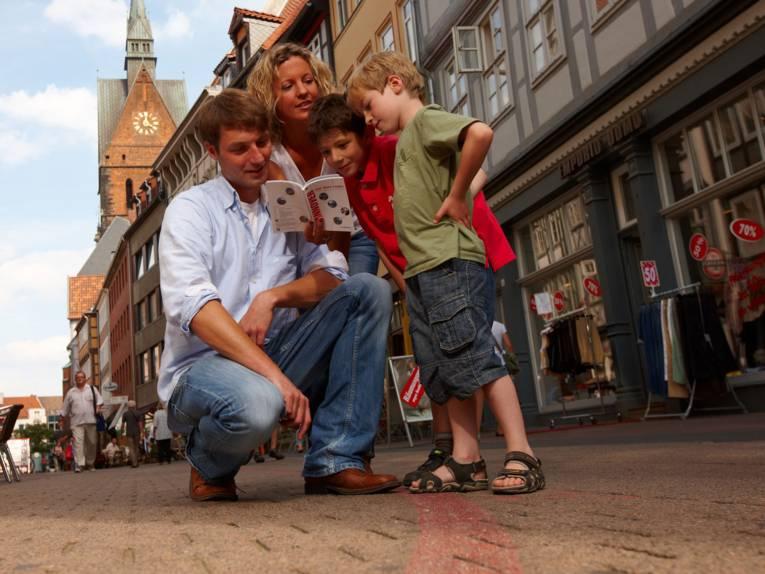 Eine Familie schaut in eine Broschüre.