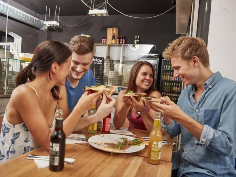 Zwei Frauen und zwei Männer essen Pizza