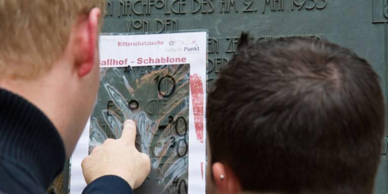 Zwei Männer untersuchen eine Steingravur.