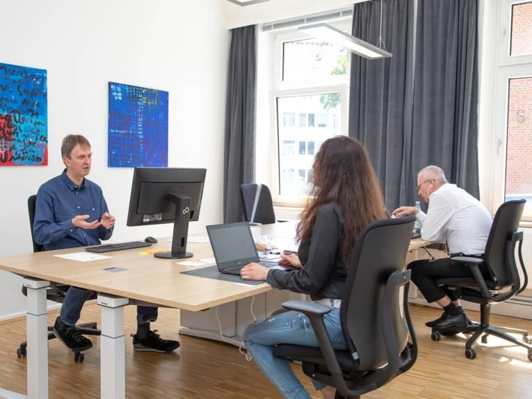 Raum mit Menschen und Rechnern.
