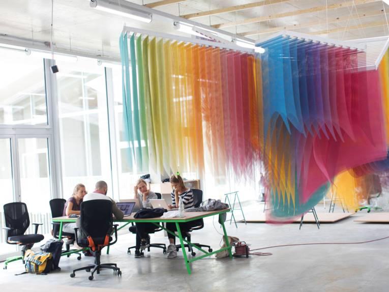 Ein Raum mit vier Menschen am Schreibtisch.