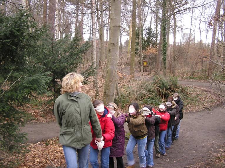 Kinder werden mit geschlossenen Augen von einer Betreuerin durch den Wald geführt, damit sie ihn mit allen Sinnen kennenlernen