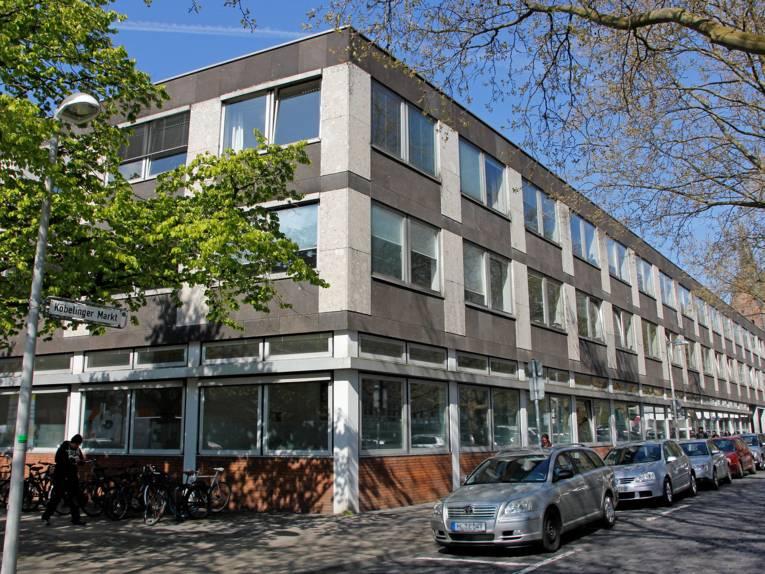 Dreistöckiges Gebäude an der Ecke Leinstraße/Köbelinger Markt mit parkenden Autos und Fahrrädern davor