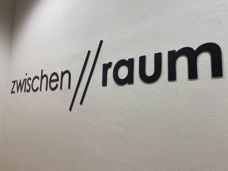 """Schriftzug an einer Wand, auf dem """"zwischen//raum"""" steht."""