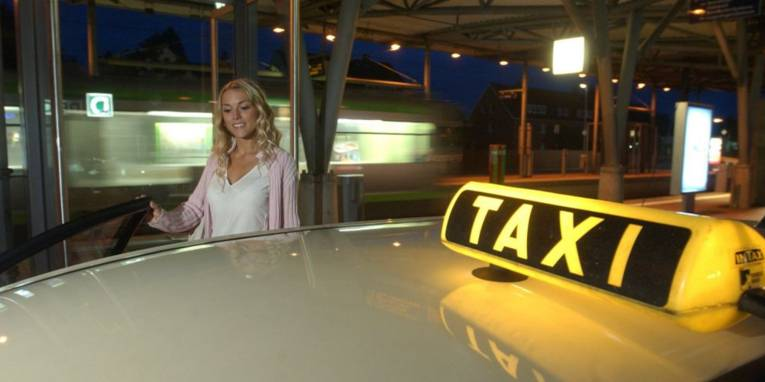 Frau, die in ein Taxi steigt