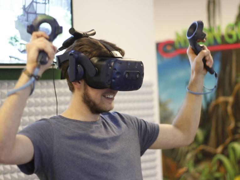 Jubelnder junger Mann mit technischer Apparatur auf dem Kopf