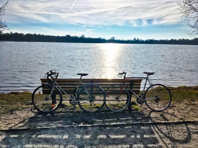 Zwei Fahrräder lehnen an einem See an einer Bank.