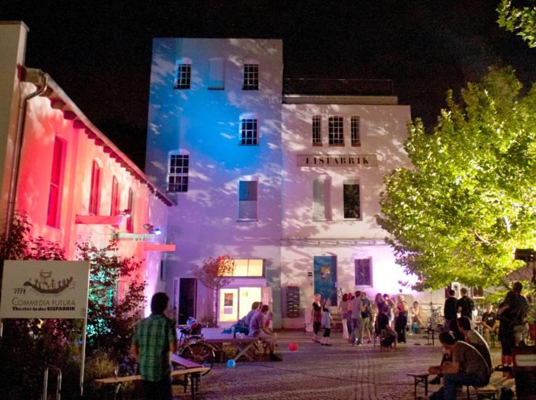 Außenansicht der Eisfabrikhalle bei Nacht: Der Hof und die Gebäude werden in verschiedenen Farben angestrahlt.