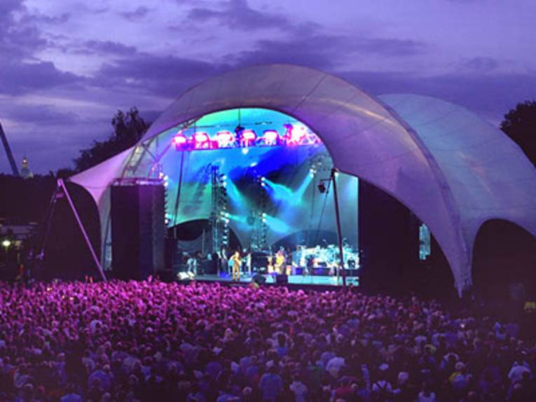 Eine Open Air-Bühne bei Nacht erleuchtet.