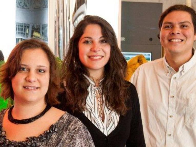 Drei lachende junge Menschen stehen nebeneinander.