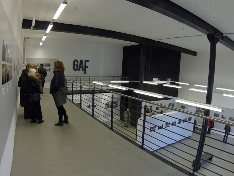 Ausstellungshalle, bei der auf zwei Ebenen Fotos an Wände und Stellwände angebracht sind.