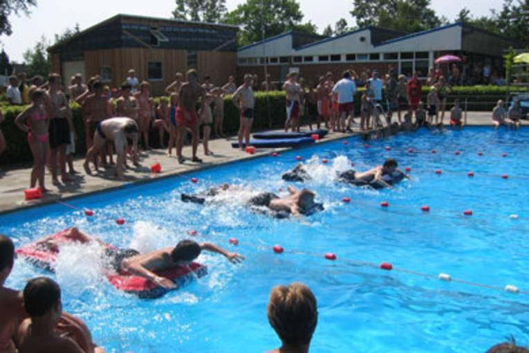 Jugendliche auf Luftmatratzen beim Wettkampf im Schwimmbad