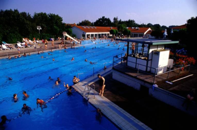 ein Schwimmbecken mit Abtrennung zwischen Schwimm- und Sprungbereich, im Hintergrund weisse Gebäude mit roten Dächern