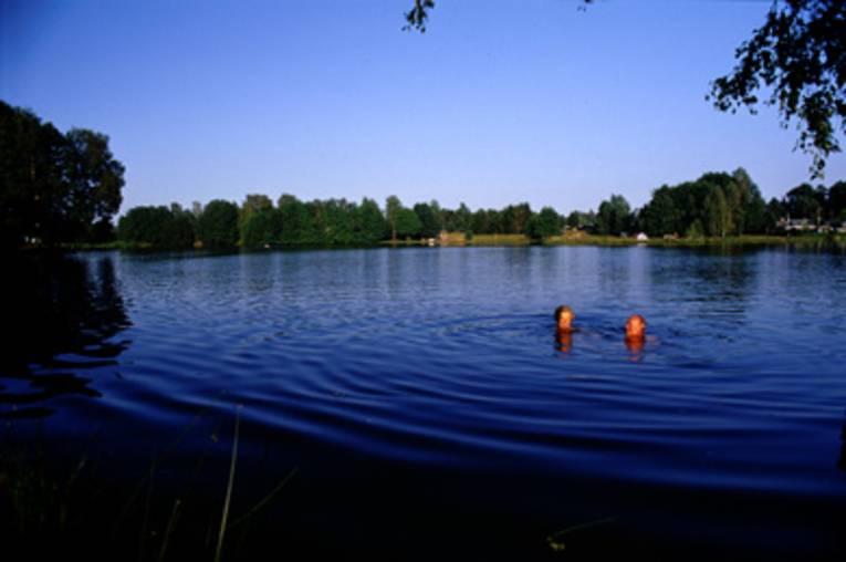 Ansicht des Sees, in dem zwei Menschen schwimmen. Im Hintergrund befinden sich viele Bäume.