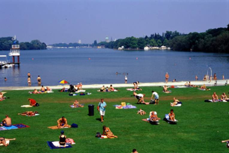 im Vordergrund liegen und sitzen Menschen in Badebekleidung auf Badetüchern auf Rasen, im Hintergrund ist ein dünner Streifen Strand und der Maschsee
