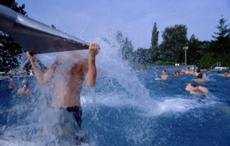 Ein Junge hat sich am Kopf der Wasserschwallbrause hochgezogen, der Körper wird vom Wasser umströmt, im Hintergrund im Wasser spielende Kinder
