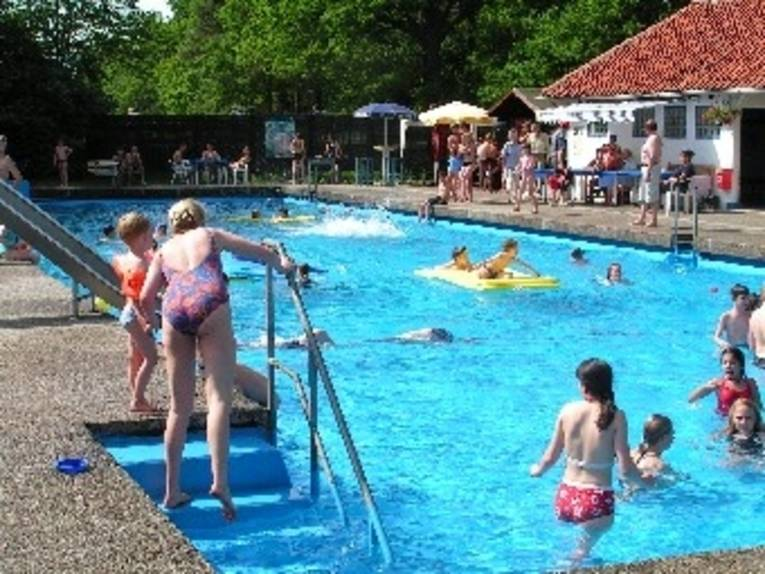 Menschen schwimmen und toben in einem Schwimmbecken unter freiem Himmel.