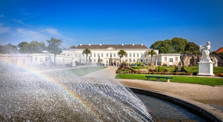 Die Sonne zaubert einen kleinen Regenbogen in den Springbrunnen im Großen Garten. Im Hintergrund ist das Schloss Herrenhausen zu sehen.