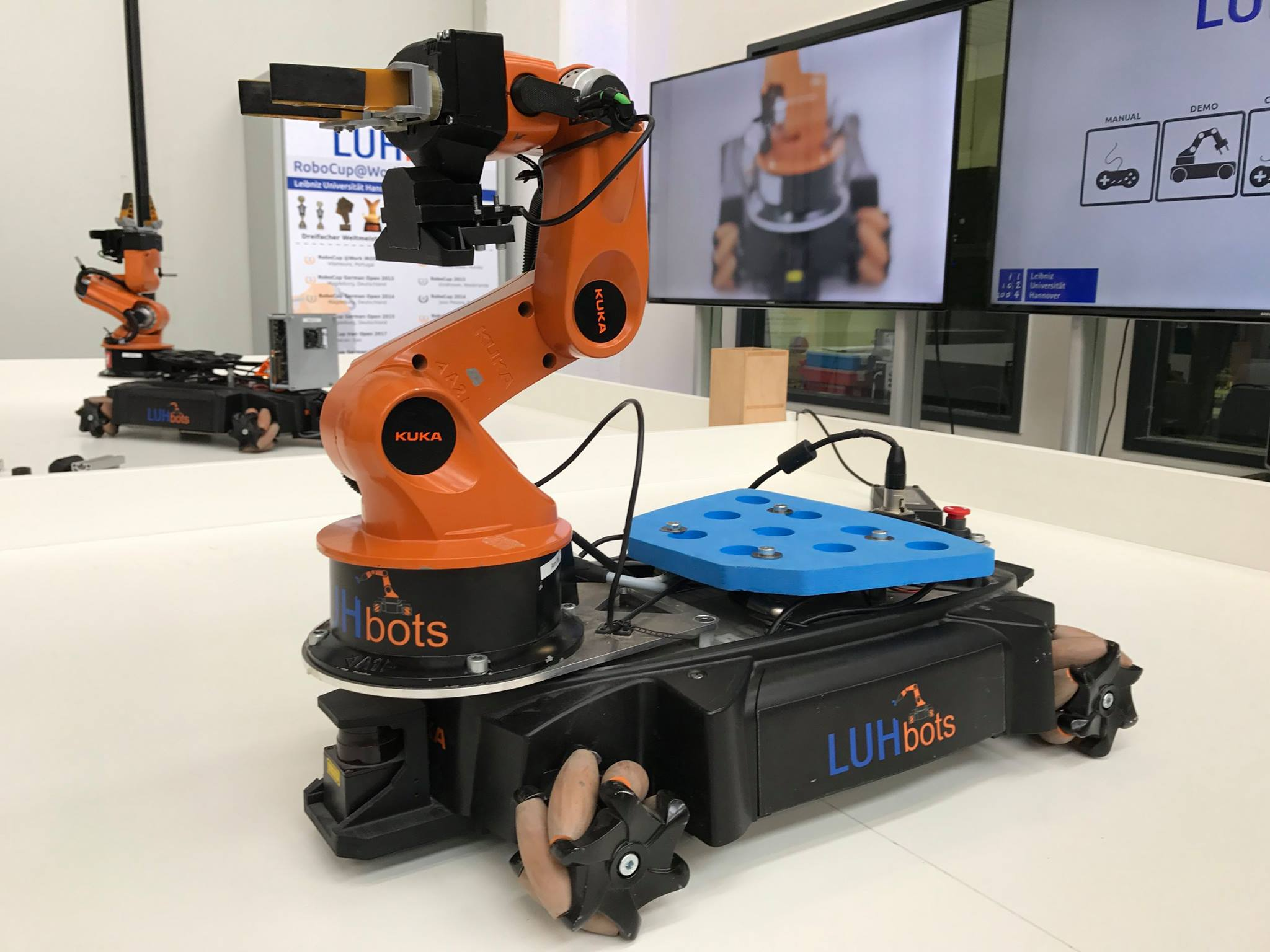 Ein Roboter vorne im Bild, hinten sind Bildschirme zu sehen.